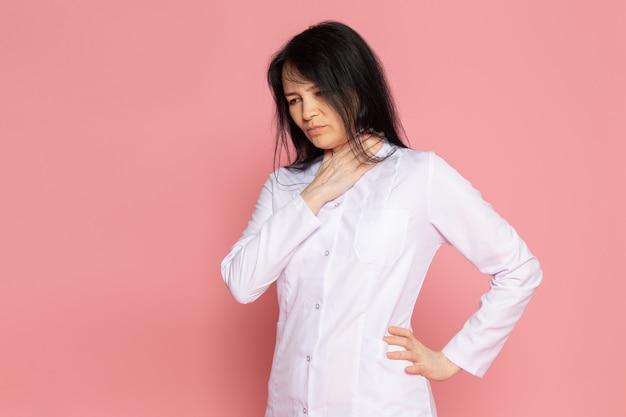 Jonge vrouw in witte medische pak met ademhalingsproblemen op roze