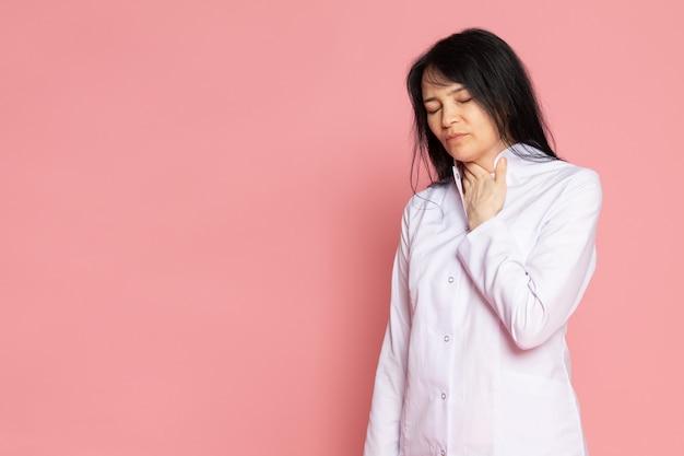 Jonge vrouw in witte medische pak problemen met haar adem op roze
