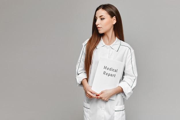 Jonge vrouw in witte medische vacht poseren met een medisch rapport in haar handen op de grijze achtergrond. kopieer ruimte voor uw tekst en product. gezondheidszorg concept.