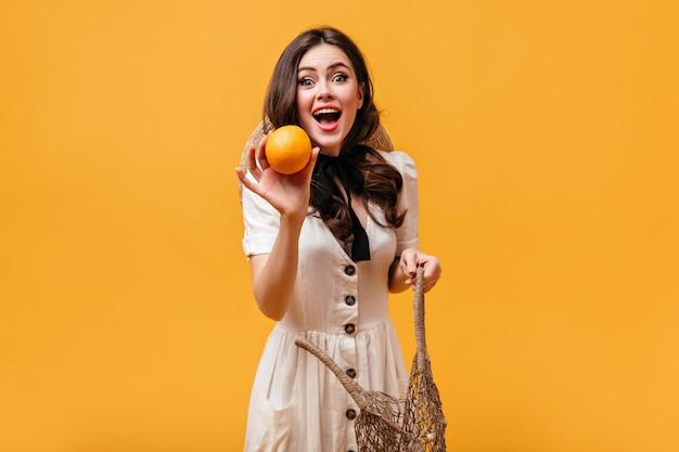 Jonge vrouw in witte outfit met zwarte strik om haar nek krijgt sinaasappel uit touwtas.