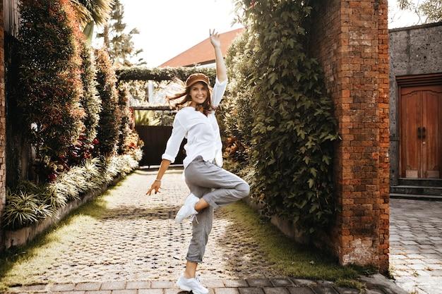 Jonge vrouw in witte sneakers, grijze broek en oversized blouse springt vrolijk tegen de ruimte van een bakstenen hek bedekt met klimop.