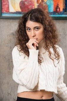 Jonge vrouw in witte trui die staat en poseert