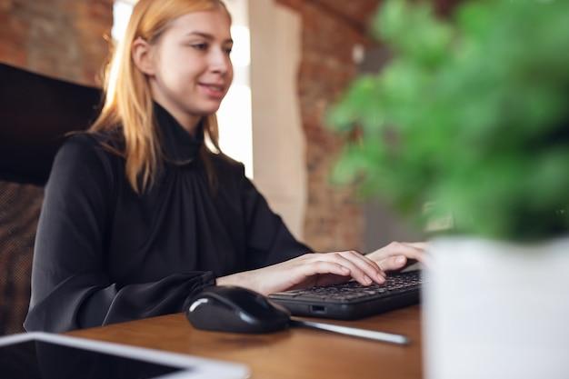 Jonge vrouw in zakelijke kleding die op kantoor werkt