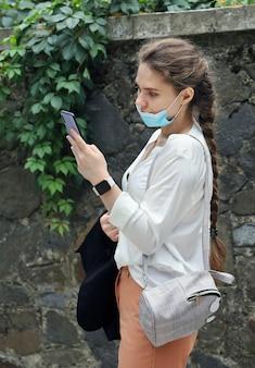 Jonge vrouw in zakelijke kleding staat buiten en kijkt naar het smartphonescherm