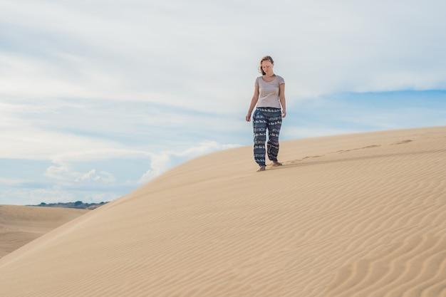 Jonge vrouw in zandwoestijn lopen alleen tegen zonsondergang bewolkte hemel. textuur van zand