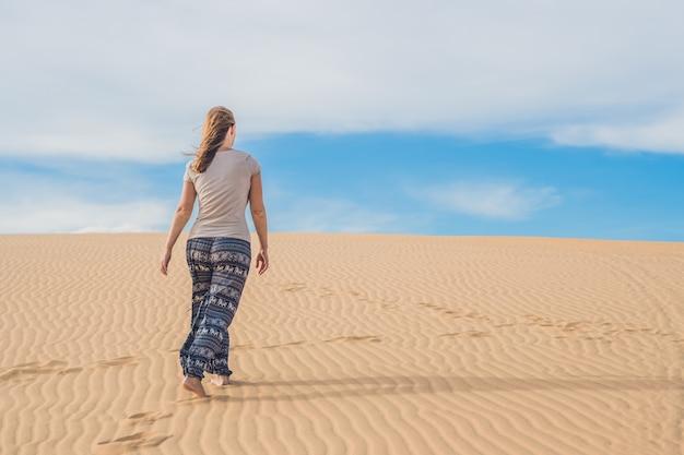 Jonge vrouw in zandwoestijn lopen alleen tegen zonsondergang bewolkte hemel. textuur van zand.