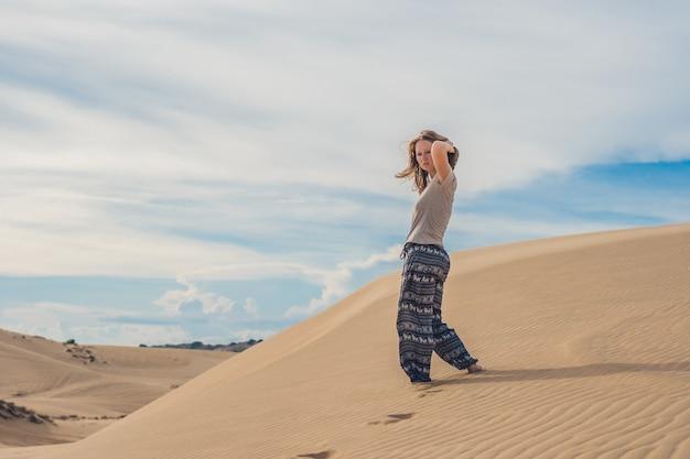 Jonge vrouw in zandwoestijn lopen alleen tegen zonsondergang bewolkte hemel