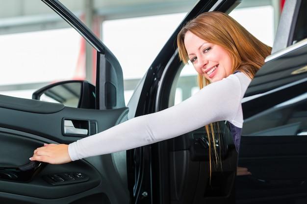Jonge vrouw in zetel van auto in het autohandel drijven