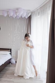Jonge vrouw in zijdebadjas wat betreft haar huwelijkskleding en het glimlachen terwijl status dichtbij het venster. trouwdag. schoonheid, mode. gelukkigste bruidsdag. geniet van elk moment.