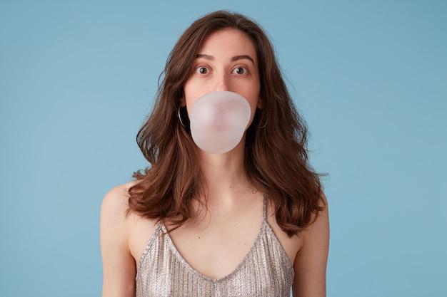 Jonge vrouw in zilveren blouse met bubblegum