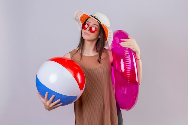 Jonge vrouw in zomer hoed dragen rode zonnebril houden opblaasbare bal en ring opzij kijken met peinzende uitdrukking denken proberen een keuze maken staande op witte achtergrond