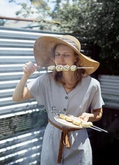 Jonge vrouw in zomer hoed en jurk grillen van vlees en groenten buiten in de achtertuin. jonge vrouw in zomerhoed ruikende gegrilde groenten buitenshuis