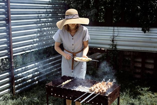 Jonge vrouw in zomer hoed en jurk grillen van vlees en groenten buiten in de achtertuin.