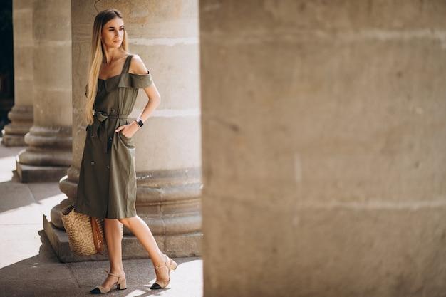 Jonge vrouw in zomer outfit door een oud gebouw