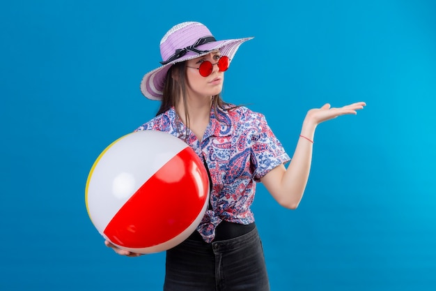Jonge vrouw in zomerhoed die rode zonnebril draagt die opblaasbare bal houdt die opzij kijkt met fronsend gezicht ontevreden status met opgeheven wapen over blauwe achtergrond
