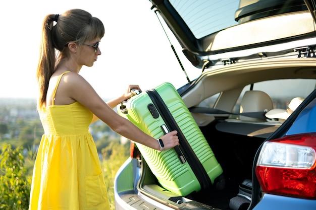 Jonge vrouw in zomerjurk groene koffer in haar auto kofferbak zetten