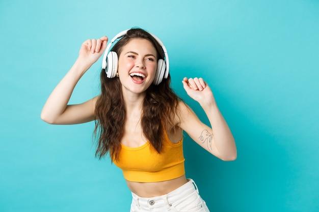 Jonge vrouw in zomerkleren die muziek luistert, een koptelefoon draagt en meezingt met haar favoriete liedje, danst in een koptelefoon, staande tegen een blauwe achtergrond.