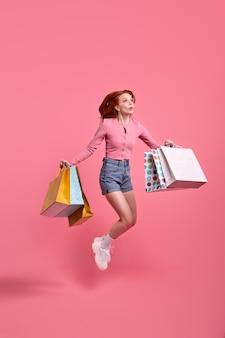 Jonge vrouw in zomerkleren houdt pakkettas vast met aankopen geïsoleerd op roze achtergrond studio s...