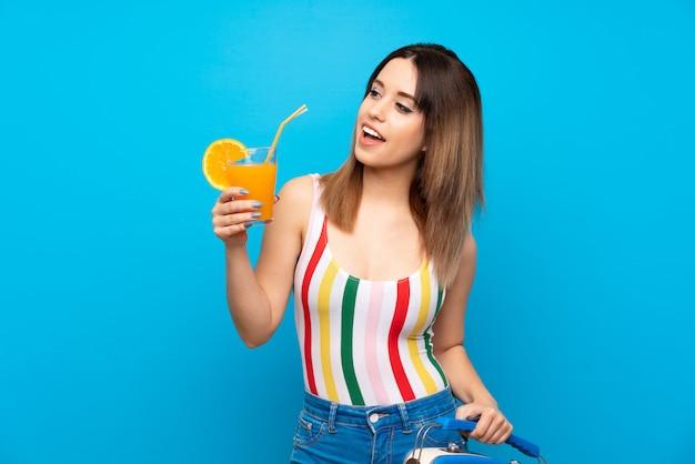Jonge vrouw in zomervakantie over blauwe muur met cocktail