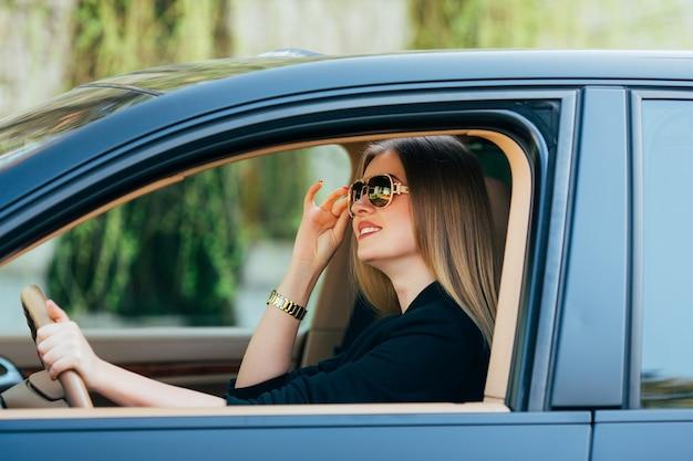 Jonge vrouw in zonnebril achter het stuur