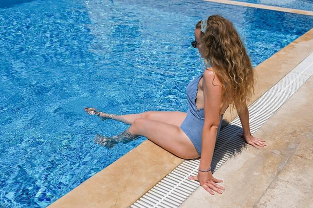 Jonge vrouw in zonnebril en bikini dichtbij het zwembad dat op vakantie zonnebaadt.