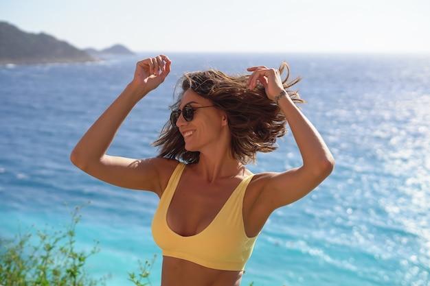 Jonge vrouw in zonnebril in een goed humeur op vakantie op het strand, genietend van een warme zomerdag