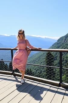 Jonge vrouw in zonnebril poseren op het observatiedek tegen de achtergrond van bergen