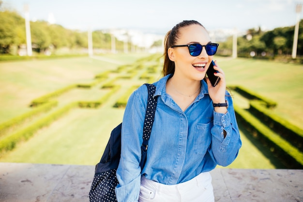 Jonge vrouw in zonnebril praten op een mobiele telefoon tegen de achtergrond van een plant