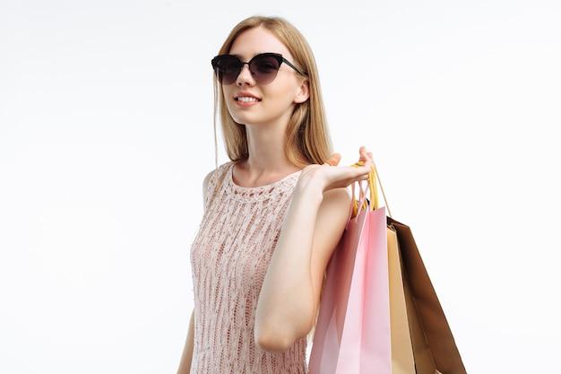 Jonge vrouw in zonnebril winkelen, die met giftzakken stellen