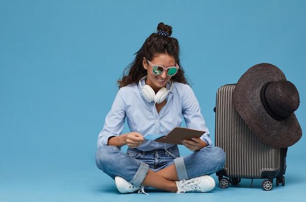 Jonge vrouw in zonnebril zittend op de vloer in de buurt van de bagage en met behulp van digitale tablet ze online tickets bestellen