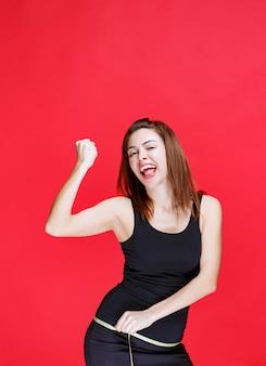 Jonge vrouw in zwart hemd die een meetlint vasthoudt, haar heupen meet en tevreden is