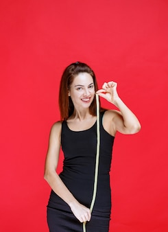 Jonge vrouw in zwart hemd met een meetlint