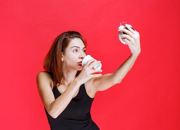 Jonge vrouw in zwart hemd met een wekker terwijl ze een kopje thee drinkt