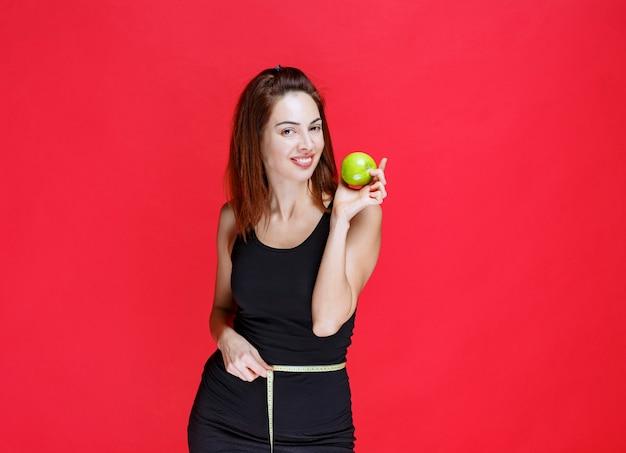 Jonge vrouw in zwart hemd met groene appels met een meetlint om haar middel