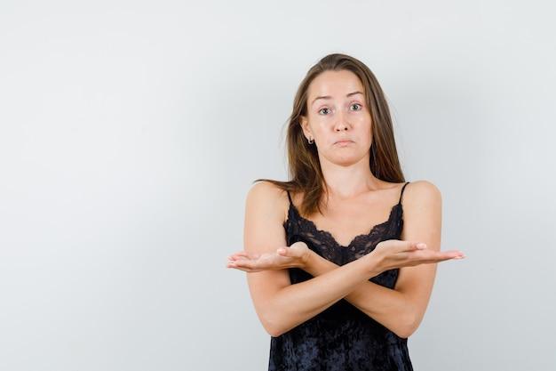 Jonge vrouw in zwart hemd spreidt de handpalmen opzij en kijkt verward