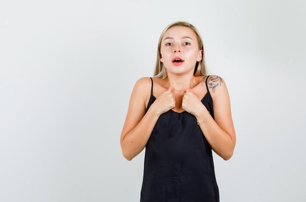 Jonge vrouw in zwart hemd wijzende vingers naar zichzelf en kijkt verward