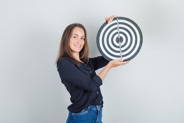 Jonge vrouw in zwart overhemd, jeansborrels die dartbord houden en vrolijk kijken