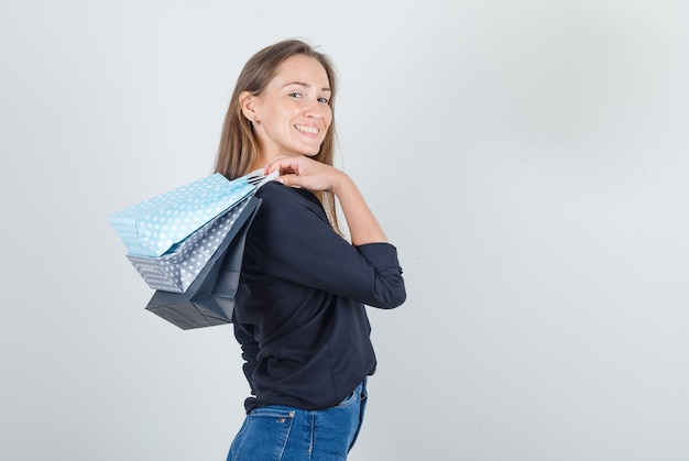 Jonge vrouw in zwart overhemd, jeansborrels die papieren zakken houden en er vrolijk uitzien