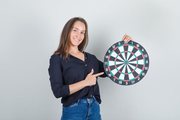 Jonge vrouw in zwart overhemd, jeansborrels die vinger richten op dartbord en vrolijk kijken