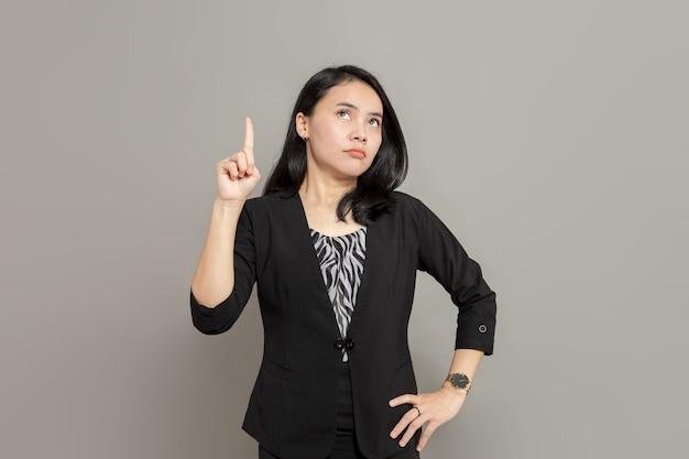 Jonge vrouw in zwart pak kijkt en wijst met één hand met vreemde gezichtsuitdrukking