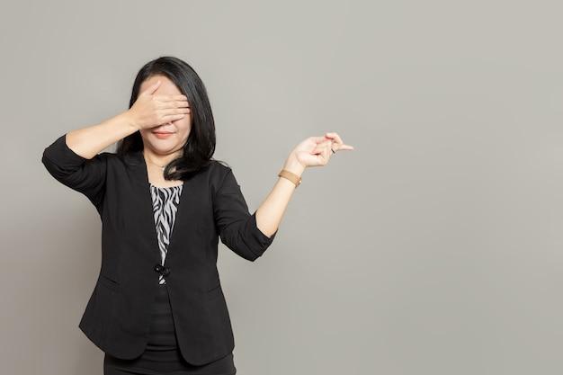 Jonge vrouw in zwart pak wijst naar rechts terwijl ze haar ogen bedekt met haar handen