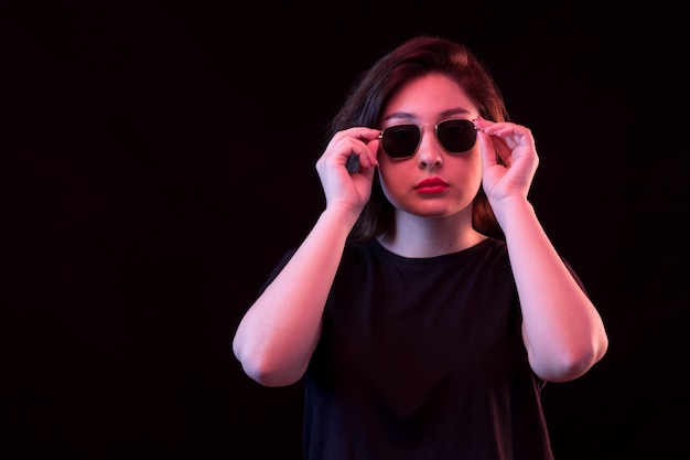 Jonge vrouw in zwart t-shirt en zonnebril die zich voordeed op de zwarte muur