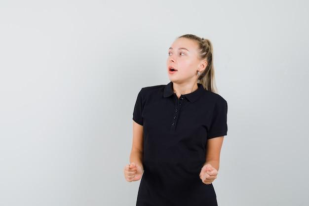 Jonge vrouw in zwart t-shirt haar armen balde als vuistpomp en optimistisch op zoek
