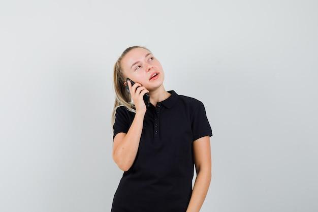 Jonge vrouw in zwart t-shirt praten aan de telefoon en kijken naar de rechterkant en peinzend kijken
