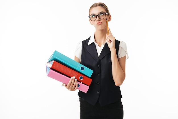 Jonge vrouw in zwart vest en bril rollen speels ogen terwijl kleurrijke mappen en potlood in handen