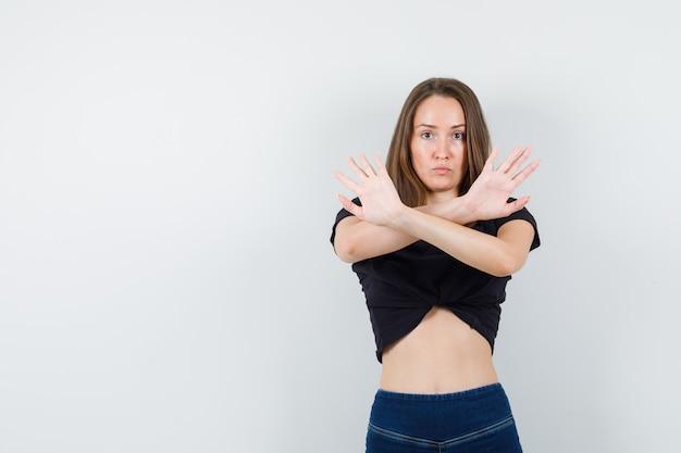 Jonge vrouw in zwarte blouse die stopgebaar met gekruiste armen toont en ernstig kijkt