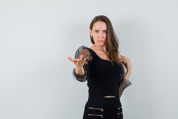Jonge vrouw in zwarte blouse en zwarte broek die hand uitrekt, uitnodigend om te komen en op zoek ernstig, vooraanzicht.