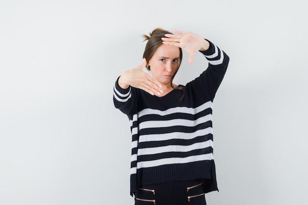 Jonge vrouw in zwarte blouse en zwarte broek die kadergebaar toont en ernstig kijkt