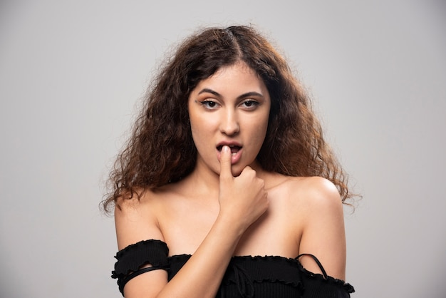 Jonge vrouw in zwarte blouse met krullend haar poseren. hoge kwaliteit foto