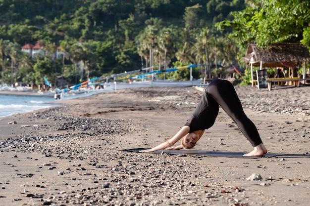Jonge vrouw in zwarte doen yoga op aziatisch zandstrand